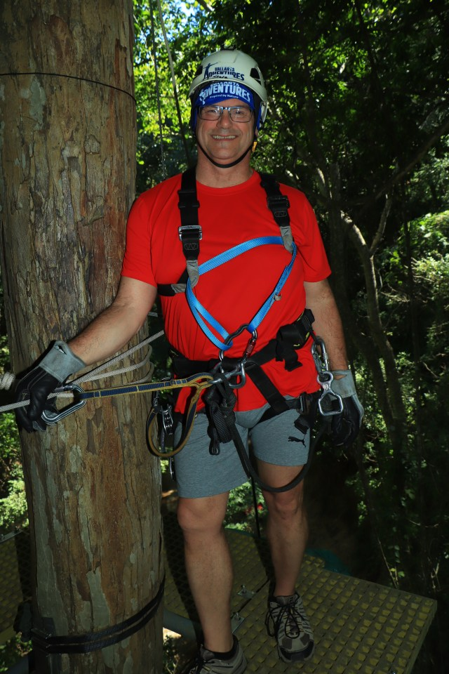 Me standing on a narrow platform around a tree, getting ready to zipline