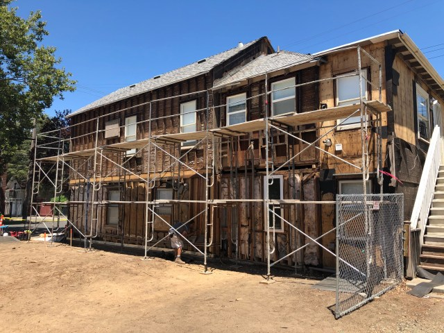 south side of house completely bare of siding and trim, with scaffolding in front of it
