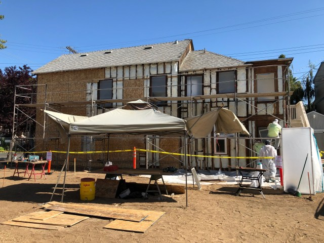 south side of house showing an array of status - insulation in, some plywood over about half, haz mat guys outs