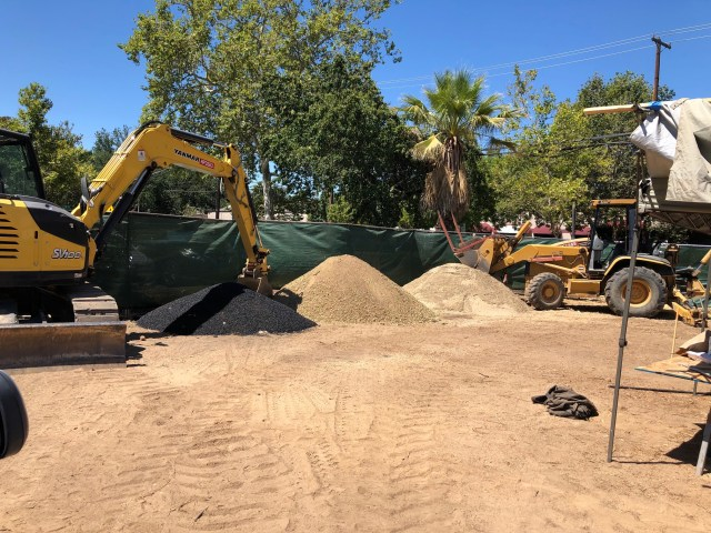 empty lot with big machinery and piles of various kinds of dirt - black, tan, a light a beige pile