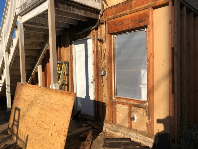 back of the house, back door of tenant unit, showing state of wood after siding off