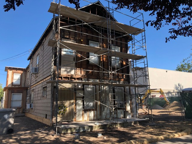 front of the house, sun behind the street trees shading it, 2nd floor all siding off, bottom floor now has insulation
