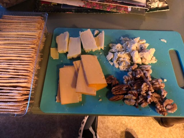 a tray of crackers on the left, with 3 kinds of cheese plus pecans on a cutting board