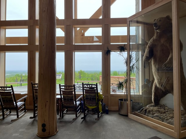 Rockers line the large windows at the end of the lobby, offering a view outside. A large stuffed bear is encased in glass on the right.