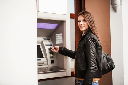 Pretty Young Woman Withdrawing Money at the Bank Machine