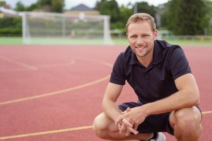 sportler macht eine pause beim training auf dem sportplatz
