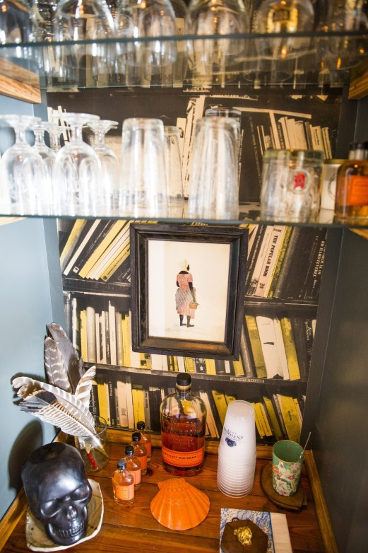 """Our bar is a small pass through between our den and dining room. The book wallpaper was my """"souvenir"""" from a trip to Paris. I think the hunt for the store was just as fun as the purchase."""