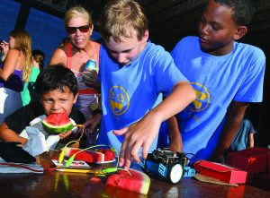 """Jacob Long, 12, of Newport, center, and Nick Lockhart, 12, of Newport, right, demonstrate their """"maker"""" prowess as Willy Mejia, 5, of Newport bites into a piece of watermelon that sends a signal to a 'makey-makey' board and onto a second piece of watermelon ultimately making the blue robot move during the FabNewport Maker Party on Sunday at the Casino Theatre in Newport. Courtesy Newport Daily News"""
