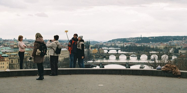 Analogue photo of a couple using a selfie stick to take a picture of themselves in front of the bridges of Prague