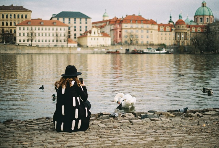 An analogue photo of a girl in a black hat and black jacket with white oblongs crouches at the waterside to take a photo of a swan. Prague