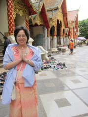"""My wife shows the proper method of doing the """"wai"""". As in many temples it's advisable to dress appropriately. That means no shorts, or sleeveless tops. You probably want to leave your best wingtips or Air Jordan sneakers at home. You'll have to take them off before entering temples and who knows if it'll be waiting when you're ready to leave. As for clothing, many of the larger temples offer appropriate clothing to use for a small price."""