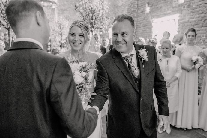father of the bride shaking the grooms hand in the tithe barn
