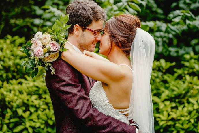 bride and groom portrait in front of greenery in park