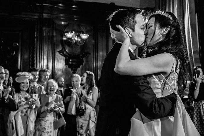 bride and groom kiss during first dance with family looking on