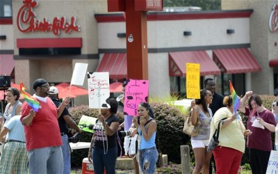 People hold signs during a gay and lesbian kiss in protest outside a Chick-fil-A restaurant