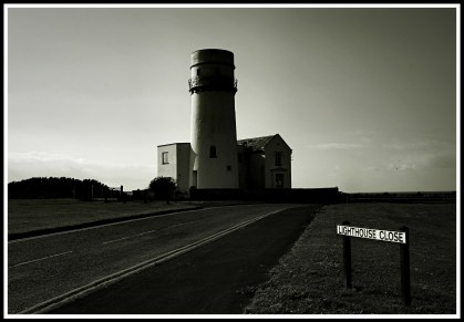 photo taken at the start of lighthouse close with the sign on the lower right and the lighthouse in the centre of the photo