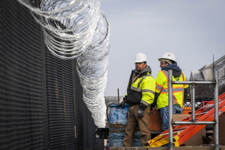 Workers install barbed wire on the fenced perimeter of the U.S. Capitol in Washington, D.C., U.S., on Friday, Jan. 15, 2021.