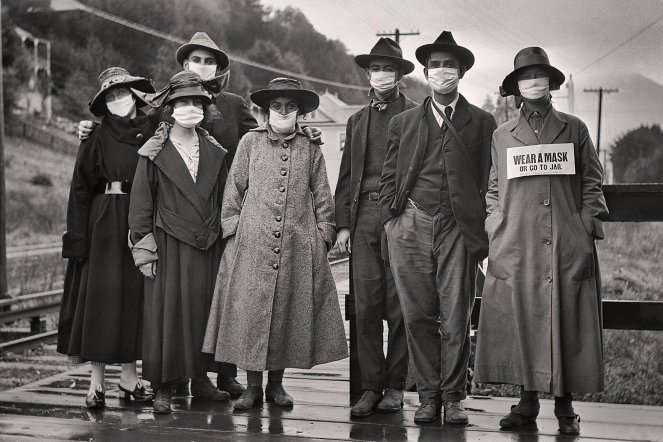 """Mask Mandates In US History - The Mask Mandate of 2020 is not the first time the US has had a mask mandate.  - Rail commuters wearing white protective masks, one with the additional message """"wear a mask or go to jail,"""" during the 1918 influenza pandemic in California.Credit...Vintage Space/Alamy"""