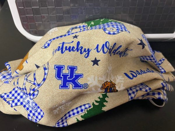 Kentucky Wildcat Christmas (Kentucky Wildcat Winter) - This wintery face mask is great for Kentucky Wildcat fans. Kentucky Wildcat Christmas Adult Size Handmade using cotton fabric I got this fabric from a local fabric shop Note: *Pattern location may vary with each mask made. My mask fit a bit bigger than most mask! My front fabric I cut 10″ wide. When it is pleated down and all the sewing is done, it is turned right-side out. Usually, the mask width comes to around 9 1/4 to 9 1/2 inches wide. Plus or minus. I also use 7 inches of elastic on each side, it is tucked inside on the inside seam. I will use either black or white elastic depending on what's in stock. Check out this Kentucky Face Mask!