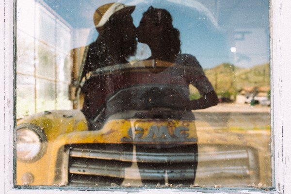 Photo of two lovers kissing with the reflection in glass.