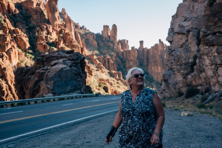 Photo of a lady enjoying the red rock views in Arizona on the roadside.