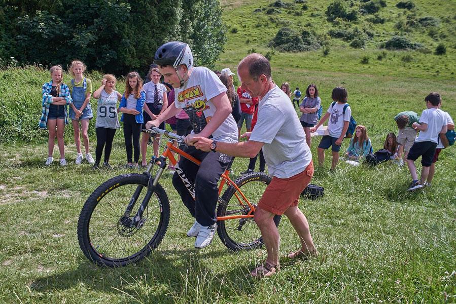 a helper assist a boy to go up a hill on a mountain bike
