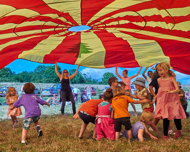 Children games playing under a parachute at the Steyning Downland Scheme Big Picnic on the Rifle Range