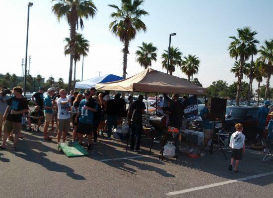 Jacksonville Jaguars fans playing cornhole at tailgate lot
