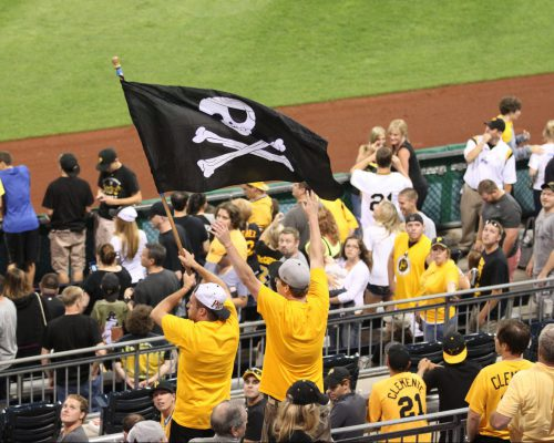 Pittsburgh Pirates fans cheering at the game and waving flag