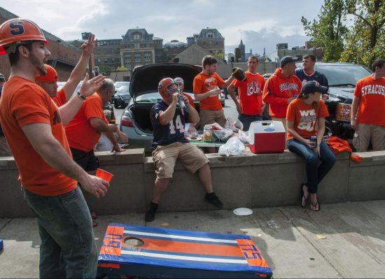Syracuse Orange fans playing cornhole at tailgate area
