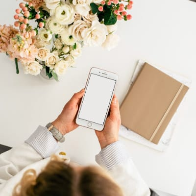 woman looking at phone at her desk