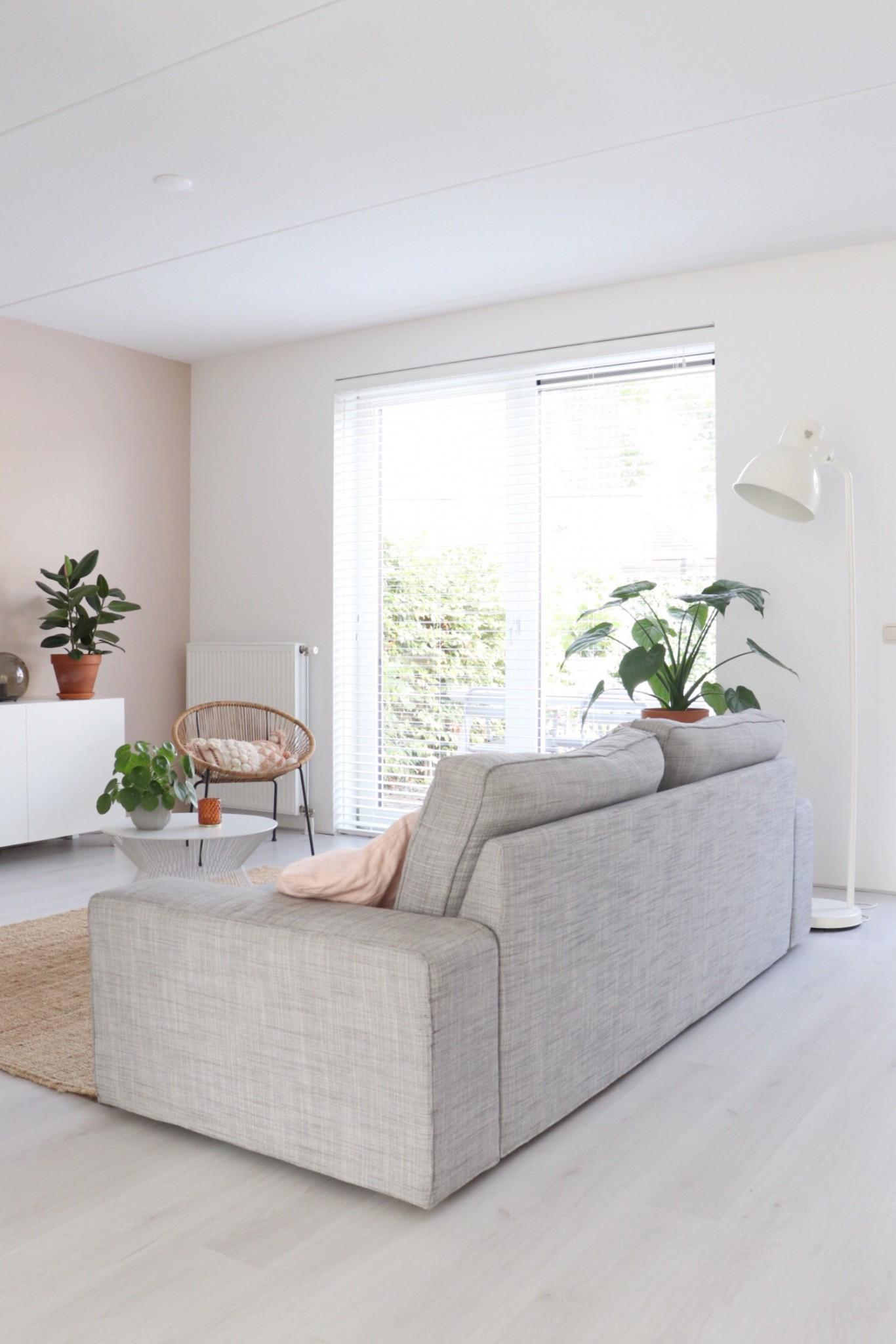 de zithoek in de woonkamer met een grijze bank, rotan stoel en planten.