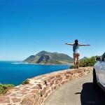 Dame med bil står på en mur