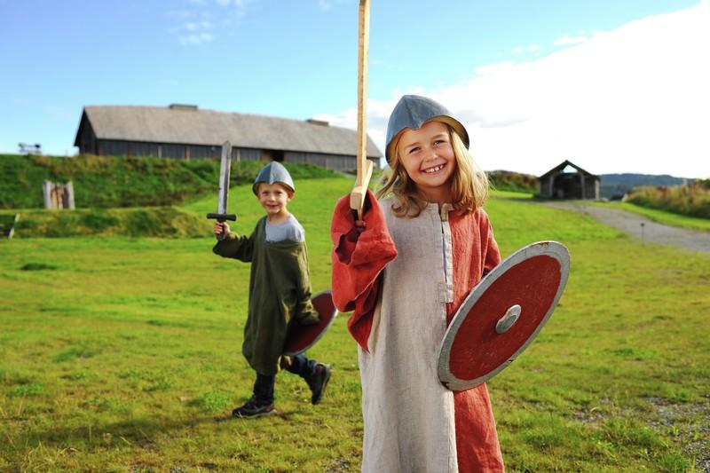 Jente og gutt kledd ut som ekte vikinger med sverd og skjold på Stiklestad. Langhus i bakgrunnen.