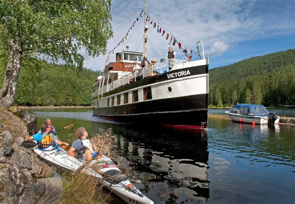"""Den gamle båten """"Victoria"""" går i fast rute på Telemarkskanalen. Passerer her tre mennesker i hver sin kano."""