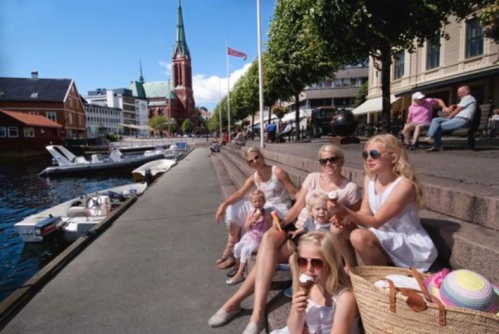 Sommerkledde jenter sitter og spiser is på bryggekanten i Pollen i Arendal. Båter i havna.