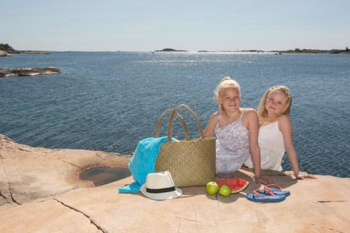 To jenter sitter på et svaberg utenfor Kristiansand. Har med kurv med mat, solhatt og frukt.