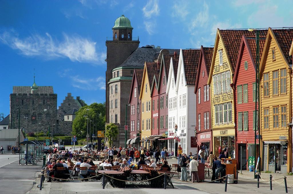 Masse folk på Bryggen i Bergen. Uteservering og gamle vernevedige hus.