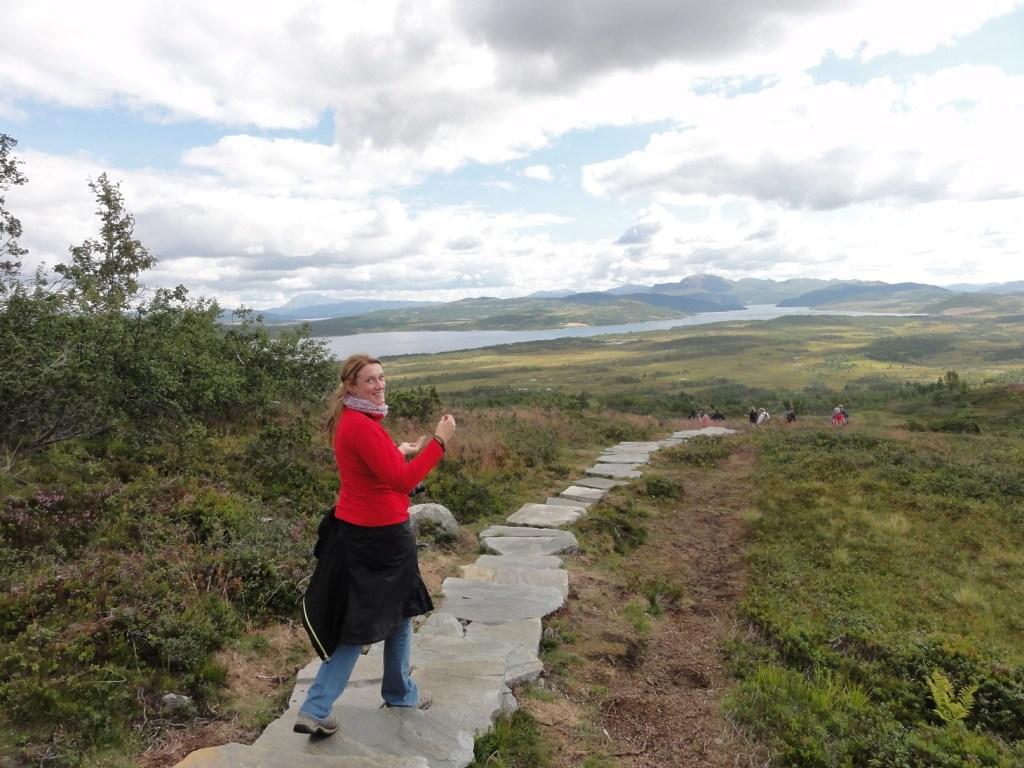 Dame i rød genser går på tur på en steinlagt sti. Stedet er falkeriset i Rauland. Lettere overskyet vær.