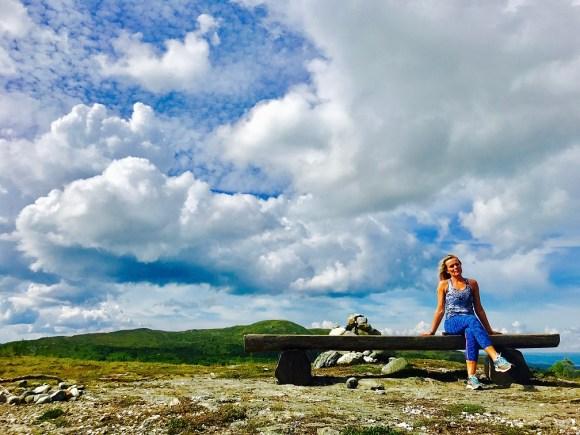 Dame sitter og tar en hvil på en benk på vei til Hårskallen i Levanger. En varde kan ses rett bak henne. Det er sommer og klarvær.