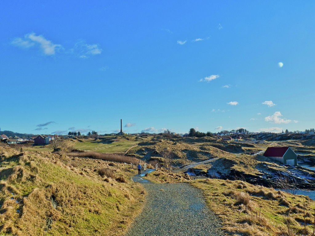 Kyststien i Haugesund med riksmonumentet Haraldhaugen i sikte. Solskinn og små flekker med snø.