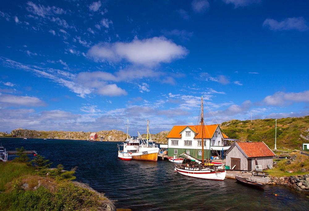 Kystlandskap med fiskeskøyte og seilbåt fortøyd ved brygge. Typisk skjærgård utenfor Haugesund.