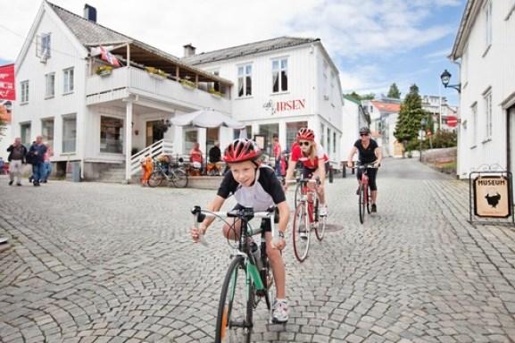 To barn og en voksen på sykkel gjennom Grimstad sentrum. Hvite hus og brosteinsbelagte gater.