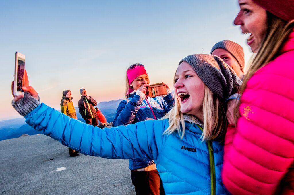 Flere unge jenter i fargerike boblejakker tar en selfie på toppen av Gaustatoppen.