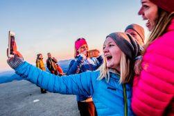 Ungdommer tar en selfie på Gaustatoppen. Smiler og ler.