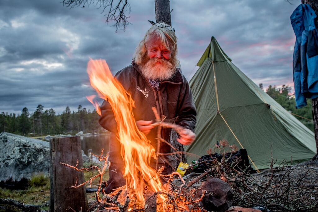 Mann med skjegg varmer seg på et bål i Femundsmarka. Grønn lavvo i bakgrunnen. Har slått leir.