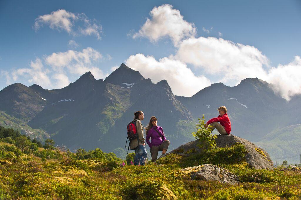 Tre personer tar seg en velforjent hvil under en fottur i Lofoten. Mektige fjell i bakgrunnen. Sol og blå himmel.