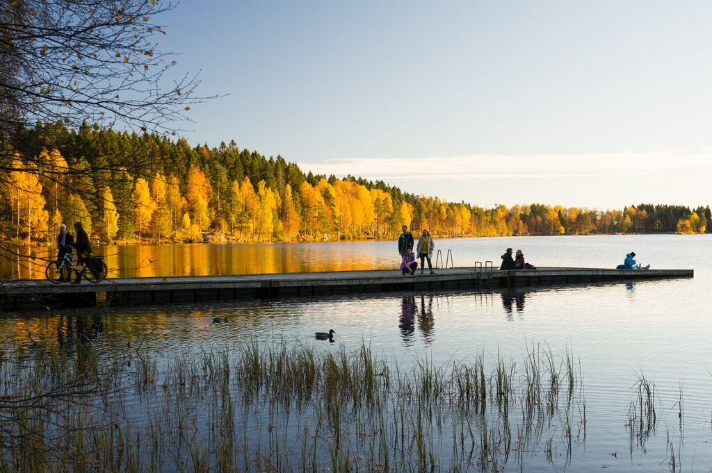 Flere personer ute på tur på en brygge i Sognsvann i Oslo. Det er vakre høstfarger.
