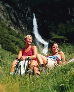 To sommerlig kledte damer tar en pust i bakken i Aulandsdalen med en foss i bakgrunnen.