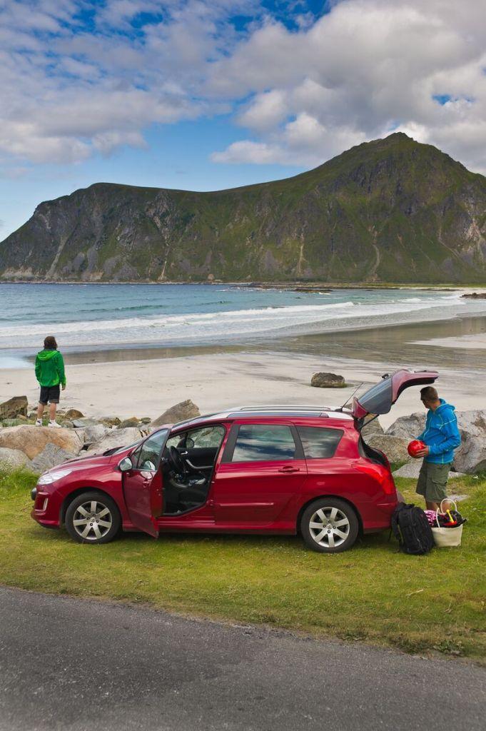Et ungt par på bilferie i Lofoten. Stoppet for en rast ved stranda i Ramberg.